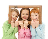 Three happy smiling kids looking through picture frame — Stock Photo