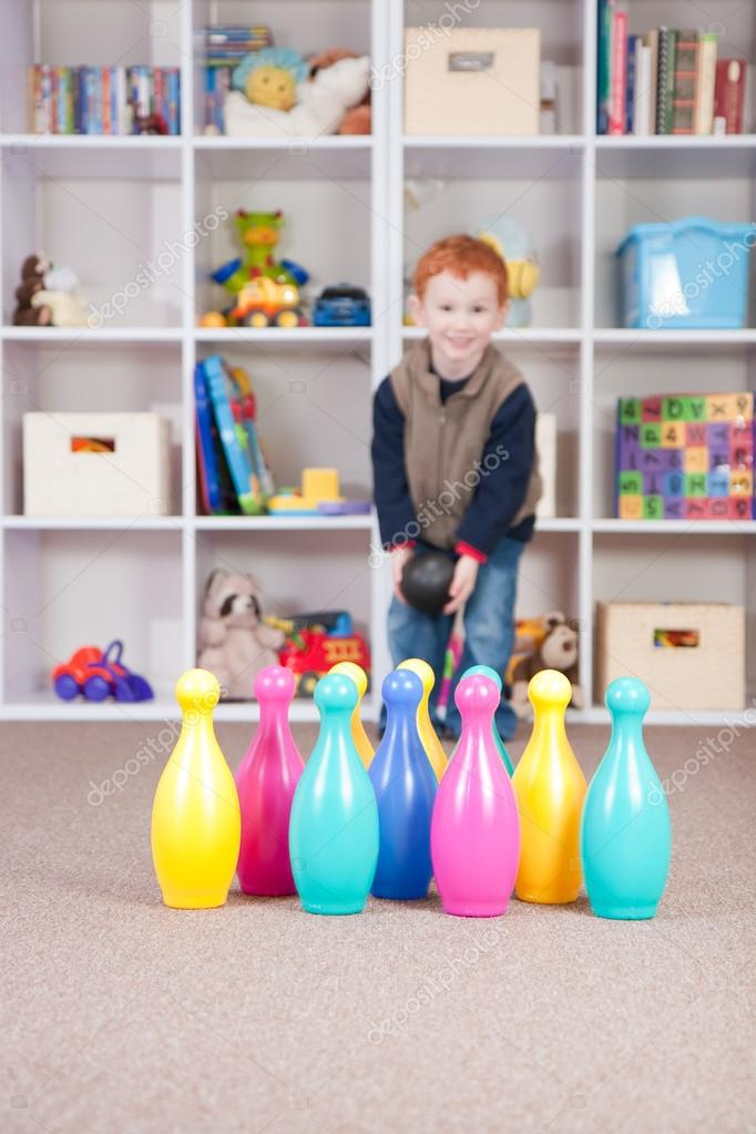 Boy playing ten pin bowling in play room  Stock Photo #12743680