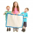 Happy kids holding blank painted sign — Stock Photo