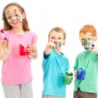 Happy messy kids with paint brushes — Stock Photo