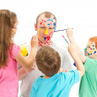 Family with kid painting with brushes on dad — Stock Photo #14416343