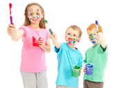Smiling messy kids with paint brushes — Stock Photo
