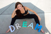 Woman SIts on Concrete Pondering Dreams Colorful Block Letters — Stock Photo