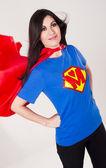 Hrdá máma sportovní červenou pláštěnku a super hrdina hrudníku prsu deska — Stock fotografie