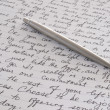 Stainless Steel Pen Laying on Written Page - Foto Stock
