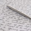 Stock Photo: Stainless Steel Pen Laying on Written Page