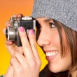 Hip Woman Snaps a Picture with Vintage Camera - Stock Photo
