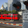 downtown scene at railroad crossing red trolley car passing sign — Stock Photo