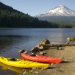 Red Yellow Kayaks on Shore Trillium Lake Mount Hood Oregon - Stock Photo