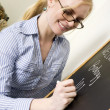 Stock Photo: Teacher Writes Message on ChalkBoard Saying Welcome to Biology