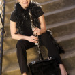 Female Street Performer Sits on Steps Clarinet Case With Tips - Stock Photo