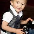 Happy Young Boy in Vest Plays Around With Vintage Camera — Stock Photo #24380681
