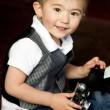 Stock Photo: Happy Young Boy in Vest Plays Around With Vintage Camera