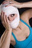 Frau hält gesicht erste hilfe gaze kopfverletzung schmerz gewickelt — Stockfoto
