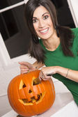 Excited woman prepares Halloween Pumkin carving it with a knife — Stock Photo