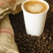 Foto de Stock  : Cappuccino To Go Paper Cup Burlap Bag Roasted Coffee Beans