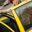 Постер, плакат: Woman Smiling Wearing Bright Accents Enters Taxi Cab Automobile