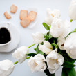 Cup of black coffee with cookies and white tulips on background — Stock Photo