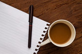 Coffee with note and pen on wood background — Stock Photo