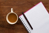 Coffee with note and pen on wood background — Стоковое фото
