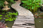 Stone and wood walkway on water in the park — Stockfoto