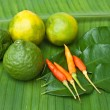 Stock Photo: Chilli kaffir and lemon lime on green banana leaves.