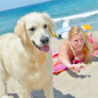 Blond girl with dog on the beach — Stock Photo