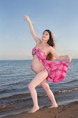 Bella donna incinta in bikini in una spiaggia sull'oceano — Foto Stock