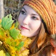 Royalty-Free Stock Photo: Close up portrait of autumn woman in knitted beret with maple leaves on nat