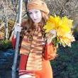 Beautiful woman in knitted clothes in a full-length with a bouquet of maple - Stock Photo