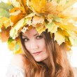Stock Photo: Beautiful fall woman. Portrait of girl with autumn wreath of maple leaves