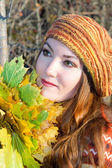Close up portrait of autumn woman in knitted beret with maple leaves on nat — Stock Photo