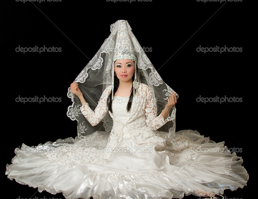 Asian bride in the Kazakh wedding white dress with a veil on his face, isolated black background — Stock Photo #12529992