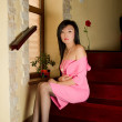 Kazakh beautiful woman in a pink suit  on stairs at home — Stock Photo