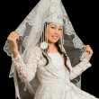 图库照片: Kazakh bride in wedding white dress with veil on his face, isolated blac