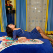 Asian kazakh woman with long hair  lying on the bed — Stock Photo