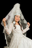 Kazakisk brud i bröllop vit klänning med en slöja på hans ansikte, isolerade blac — Stockfoto