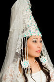 Beautiful woman in the Kazakh national wedding white dress on a black back — Stok fotoğraf