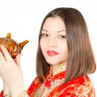 Asian woman drinking Chinese tea from the teapot in Kimono on a white backg - Stock Photo