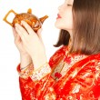 Stock Photo: Asiwomdrinking Chinese tefrom teapot in Kimono on white backg