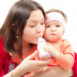 Young mother feeds child girl with a bottle with infant formula on bad. The — Stock Photo #12596077