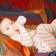 Pretty baby girl with infant formula in bottle  on bad. The concept of chil — Stock Photo