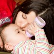 Stock Photo: Young mother feeds child girl with bottle with infant formulon bad. The