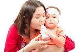 Young mother feeds child girl with a bottle with infant formula on bad. The — Stock Photo