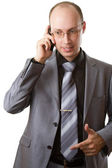 Attractive successful business man holding mobile phone and finger pointin — Stock Photo