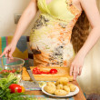 Beautiful pregnant woman with fresh green vegetables on the house kitchen — Stock Photo
