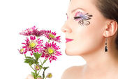 Pretty young woman with bodyart butterfly on face with flower chrysanthemu — Stock Photo