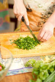 Woman s hands cutting fresh onions, dill, parsley on kitchen Focus on gree — Stock Photo