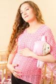 Pregnant woman with long hair and toy Teddy bear near a crib — Stock Photo