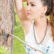 Portrait of beautiful young woman near tree in summer park — Stock Photo